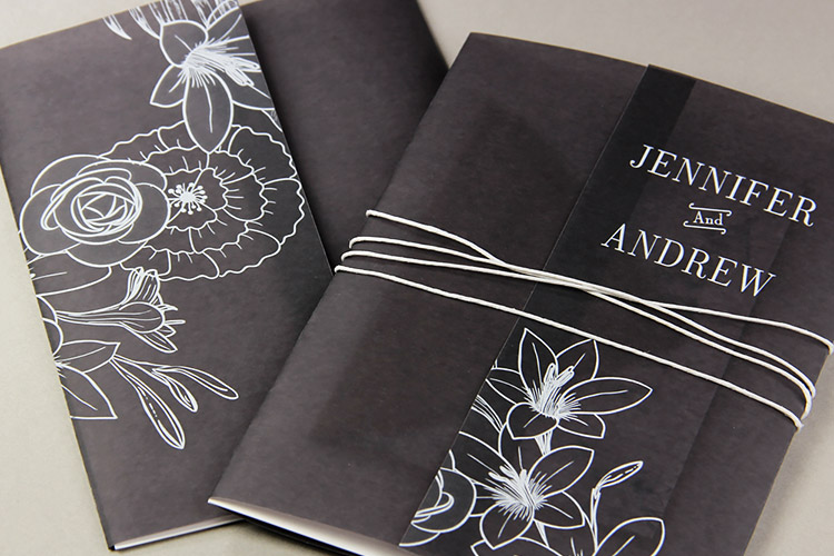 Black vellum wrapped invitations. Vellum wraps printed with white floral pattern and tied with twine