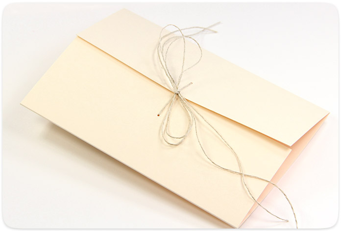 Punch holes in gatefold flaps. Run ribbon, string or twine through them and tie into a knot or bow to close