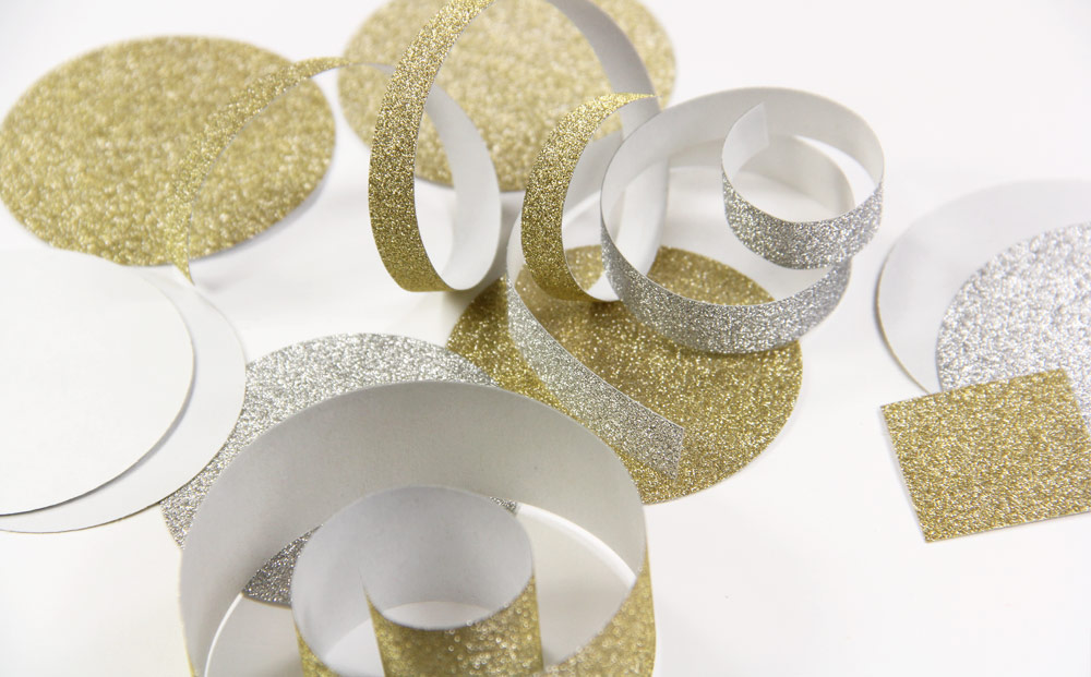 Confetti made with MirriSPAKLE glitter paper. Use a round punch for circles and strips wrapped around a cylinder-shaped object for curly pieces
