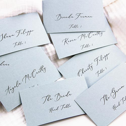 Dusty blue place cards with printed with calligraphy, handwritten font. Paper, instructions and template for place cards from LCI Paper