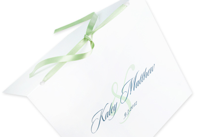 square white wedding program with blue and green text and a green ribbon