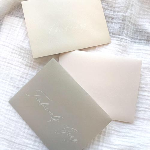 White printing on light blush, taupe and gray envelopes. White printing and addressing by LCI Paper