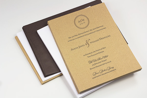 Wedding invitation printed on wood grain paper with text perpendicular to texture